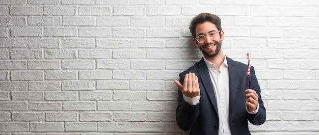Homem de negócios jovem vestindo um terno contra uma parede de tijolos brancos, convidando a vir