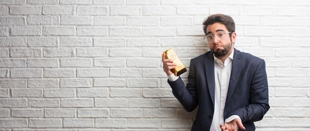 Homem de negócios jovem vestindo um terno contra uma parede de tijolos brancos duvidando e shrugging shoul