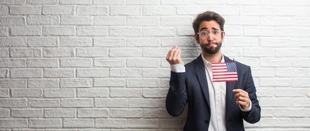 Homem de negócios jovem vestindo um terno contra uma parede de tijolos brancos fazendo um típico italiano gest