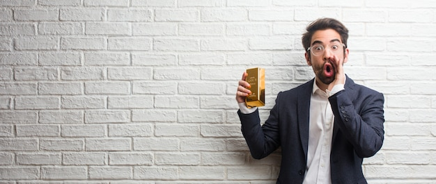 Homem de negócios jovem vestindo um terno contra uma parede de tijolos brancos gritando com raiva