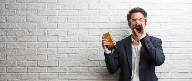 Homem de negócios jovem vestindo um terno contra uma parede de tijolos brancos gritando feliz
