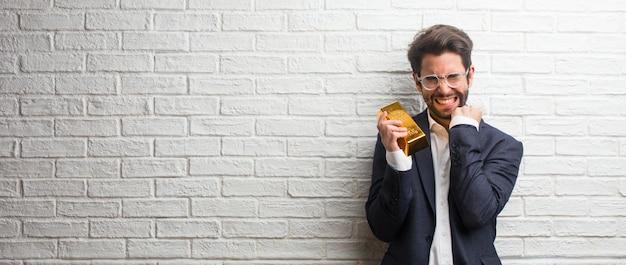 Homem de negócios jovem vestindo um terno contra uma parede de tijolos brancos muito feliz e animado