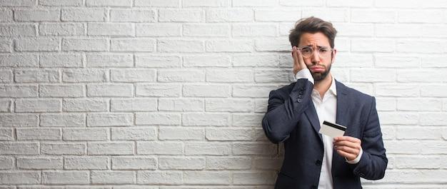Homem de negócios jovem vestindo um terno contra uma parede de tijolos brancos, preocupado e oprimido