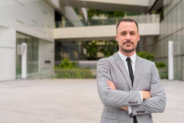 Homem de negócios latino-americano careca e bonito com os braços cruzados ao ar livre da cidade