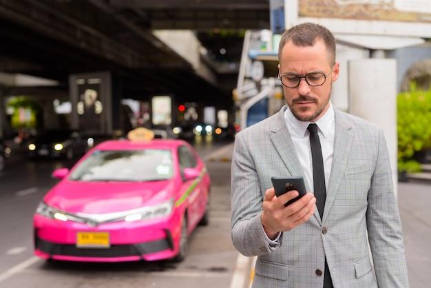 Homem de negócios latino-americano careca e bonito usando o telefone na estação de táxi