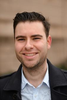 Homem de negócios latino-americano que está contra uma parede em um casaco preto. o homem sorri abertamente.