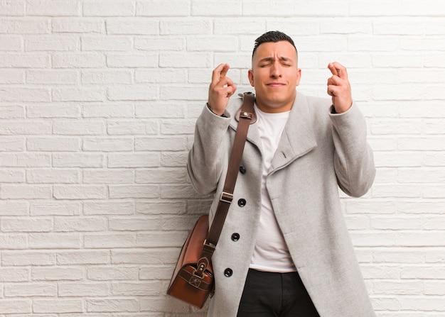 Homem de negócios latino jovem cruzar os dedos por ter sorte