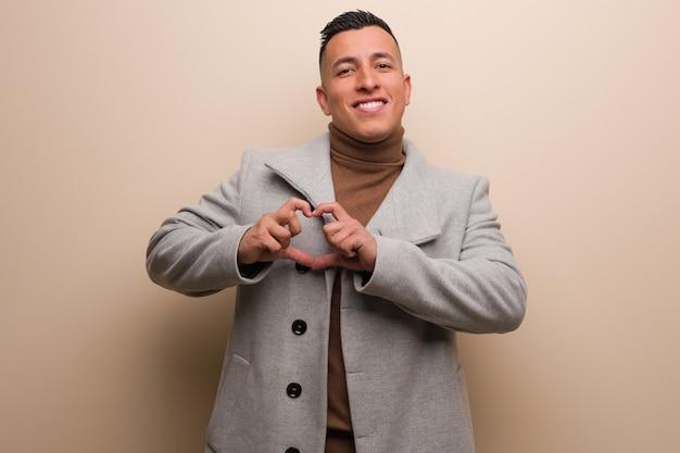 Homem de negócios latino jovem fazendo uma forma de coração com as mãos