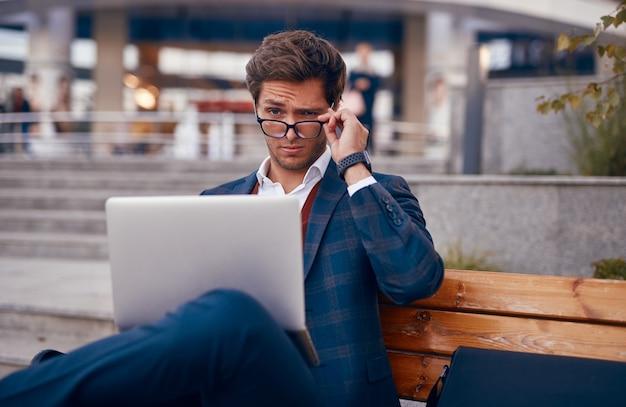 Homem de negócios legal olhando por cima dos óculos enquanto trabalhava no laptop na bancada