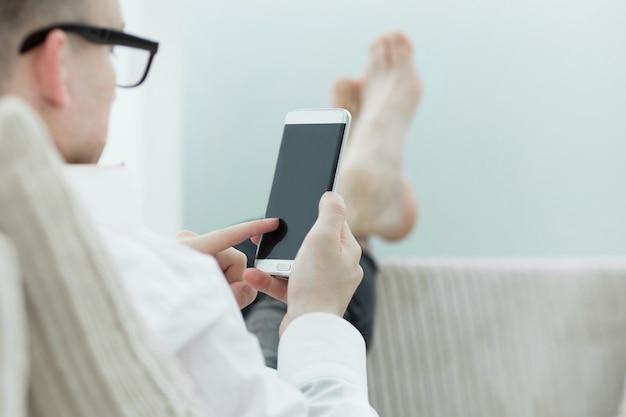 Homem de negócios, lendo notícias online em seu smartphone. pessoas e tecnologia