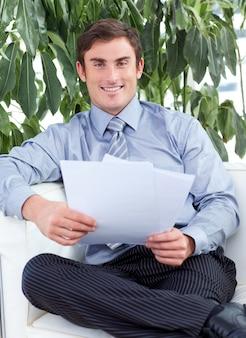 Homem de negócios lendo papéis e sorrindo para a câmera