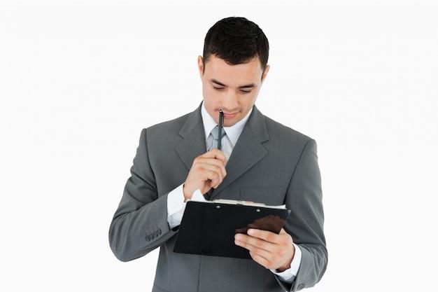 Homem de negócios lendo suas anotações em uma área de transferência