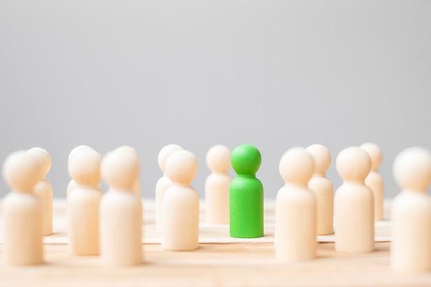 Homem de negócios líder verde com uma multidão de pessoas de madeira