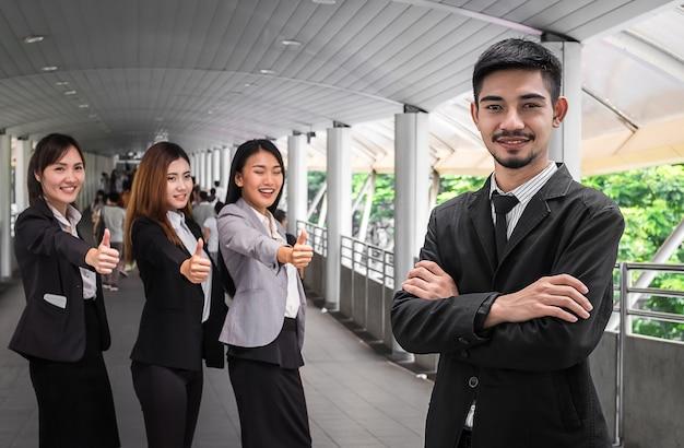 Homem de negócios, liderando um grupo corporativo de sucesso com polegares para cima