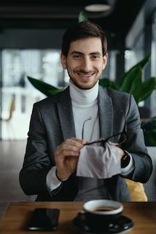 Homem de negócios, limpando os óculos com uma xícara de café