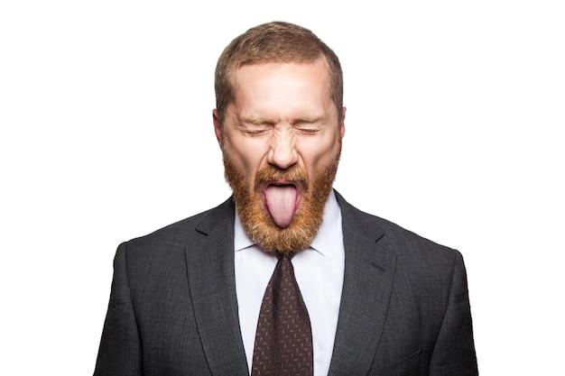 Homem de negócios louco com olhos fechados e língua. isolado no branco, olhando para a câmera.