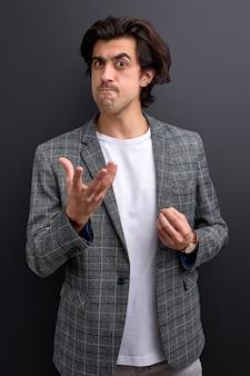 Homem de negócios louco de terno com cara de bravo enquanto repreende alguém isolado sobre um fundo preto