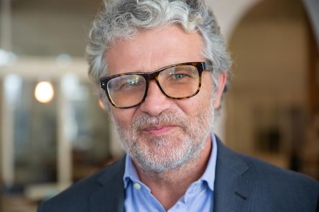 Homem de negócios maduro, amigável e feliz, usando jaqueta e óculos, posando dentro de casa, olhando para a câmera