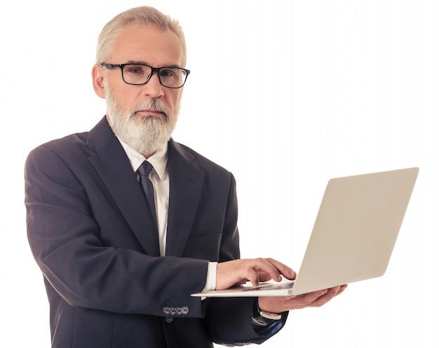 Homem de negócios maduro bonito com gadget.