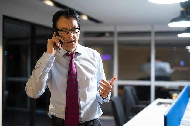 Homem de negócios maduro bonito no escritório à noite