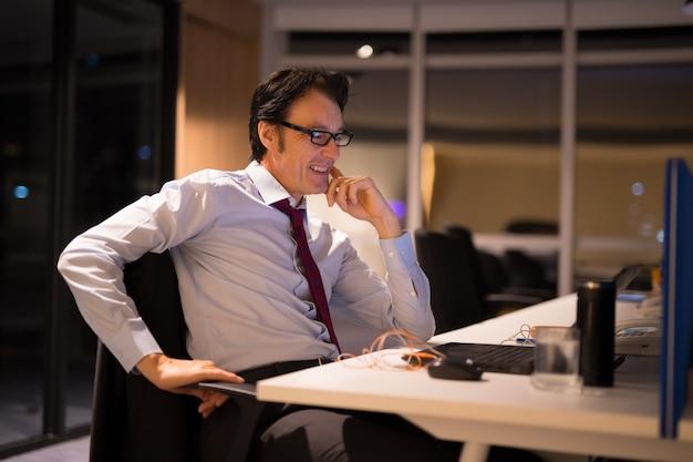 Homem de negócios maduro bonito sentado e trabalhando no escritório à noite