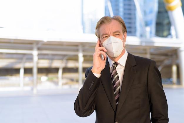 Homem de negócios maduro com máscara pensando enquanto fala ao telefone na ponte skywalk