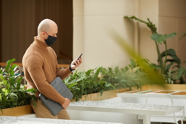 Homem de negócios maduro com máscara protetora, olhando para o celular enquanto está no prédio de escritórios