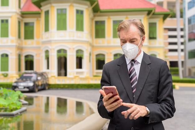 Homem de negócios maduro com máscara usando telefone na cidade ao ar livre