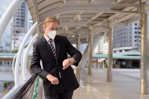 Homem de negócios maduro com máscara, verificando as horas na passarela