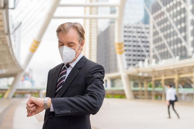 Homem de negócios maduro com máscara, verificando as horas na ponte da passarela