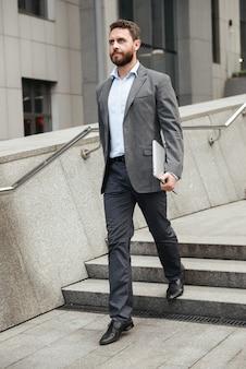 Homem de negócios maduro de corpo inteiro com roupa formal segurando um laptop prateado e andando em frente a um prédio comercial no centro da cidade