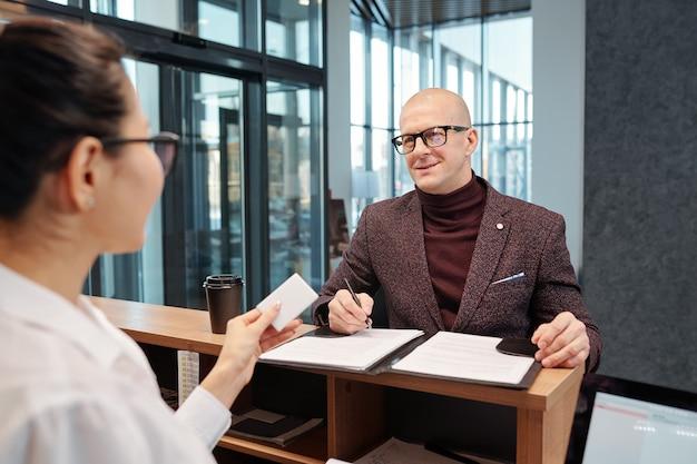 Homem de negócios maduro e careca com uma caneta, olhando para a recepcionista enquanto preenche um formulário no balcão do saguão do hotel