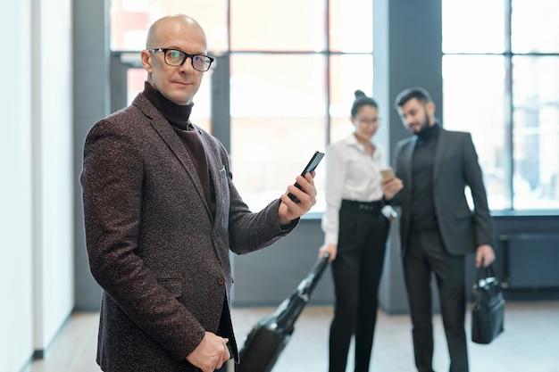 Homem de negócios maduro e careca sério com smartphone olhando para você enquanto aguarda o anúncio da partida no saguão do aeroporto