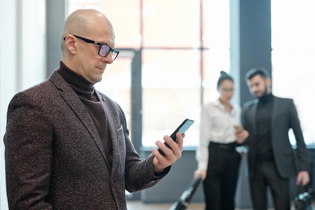 Homem de negócios maduro e careca sério em trajes formais olhando dados no smartphone enquanto espera no saguão do aeroporto