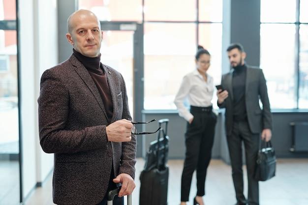 Homem de negócios maduro e confiante com óculos e mala com dois jovens colegas