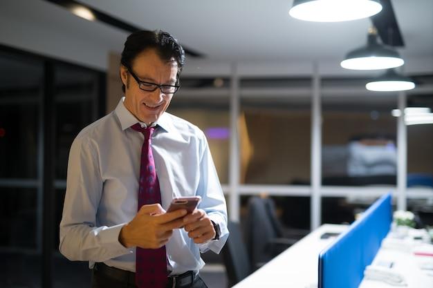 Homem de negócios maduro feliz usando telefone celular no escritório à noite