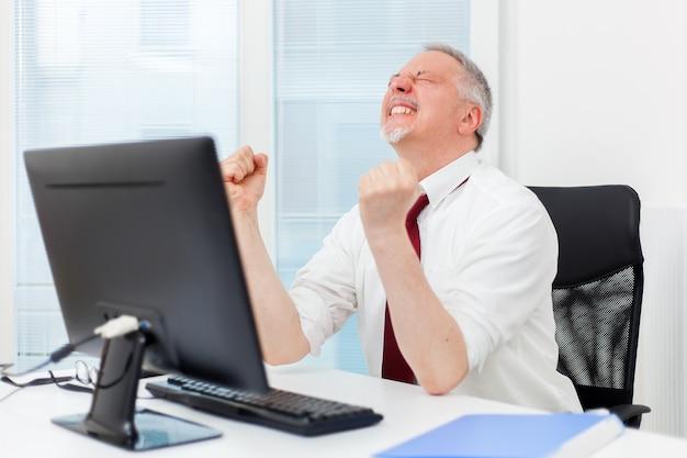 Homem de negócios maduro, levantando os braços na frente de seu pc