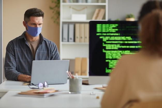 Homem de negócios maduro na máscara protetora trabalhando no laptop na mesa junto com seu colega que trabalha no escritório de ti