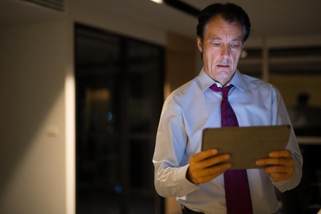 Homem de negócios maduro no escritório à noite usando tablet digital