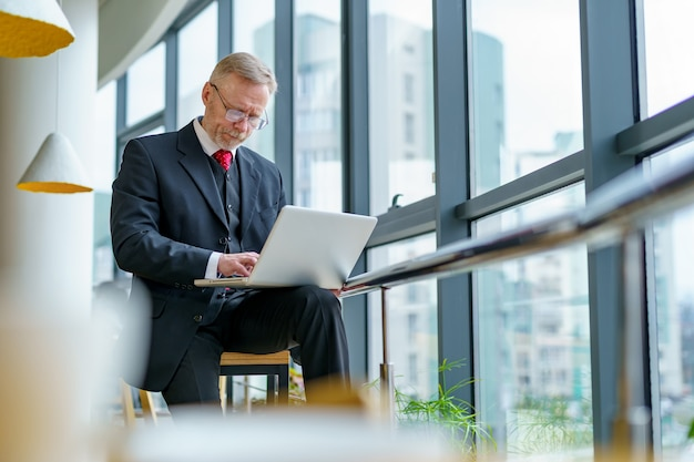 Homem de negócios maduro olhando para laptop no café de negócios. fundo de vista panorâmica da cidade.