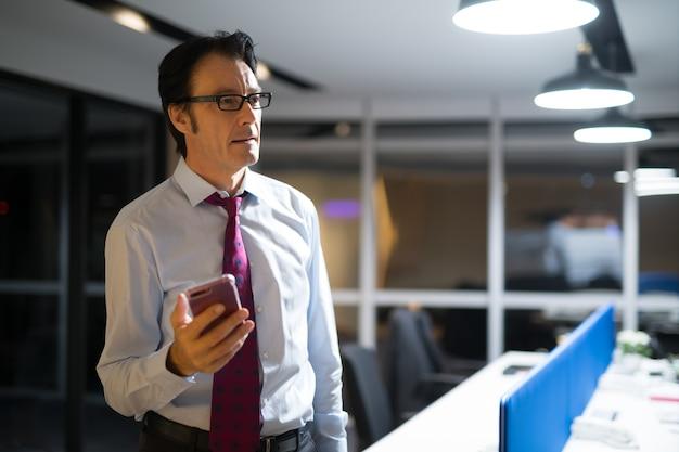 Homem de negócios maduro pensando e usando telefone celular no escritório