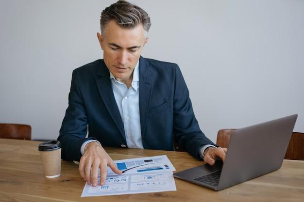 Homem de negócios maduro pensativo usando laptop, lendo relatório financeiro e analisando informações, trabalhando no escritório