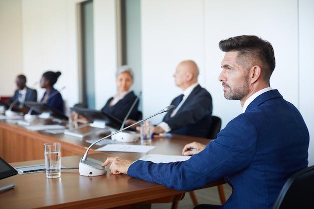 Homem de negócios maduro sentado à mesa usando o microfone para fazer um discurso para empresários durante a conferência