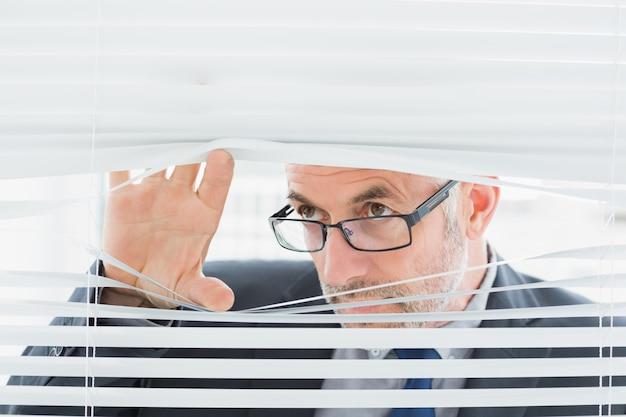 Homem de negócios maduro sério que espreita através das cortinas no escritório