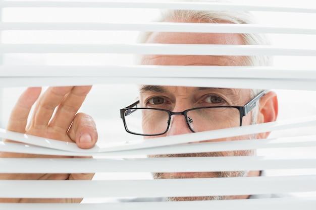 Homem de negócios maduro sério que espreita através das cortinas
