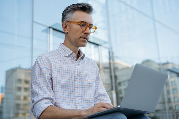 Homem de negócios maduro sério usando laptop, digitando, planejando o início