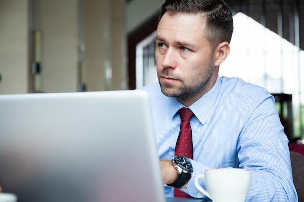 Homem de negócios maduro tomando um café em uma cafeteria e trabalhando em seu laptop