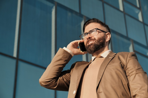 Homem de negócios maduro usando óculos falando no celular enquanto caminha pela cidade