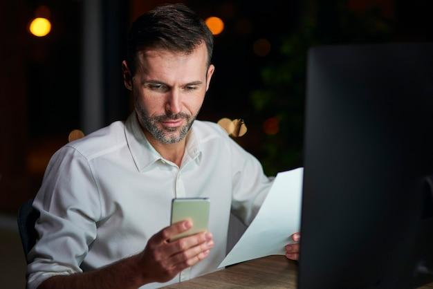 Homem de negócios maduro usando telefone celular à noite