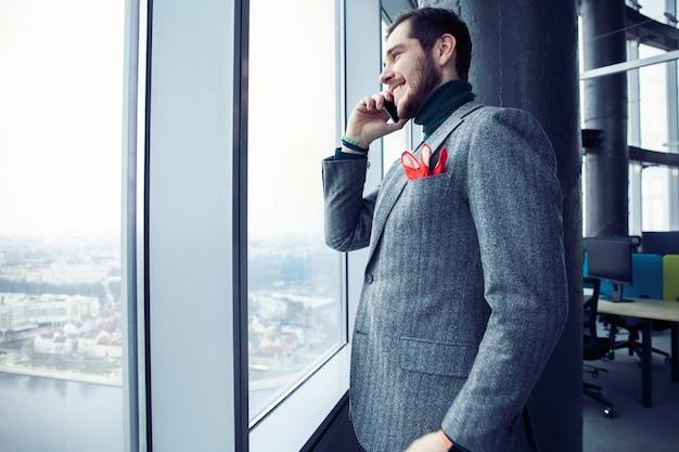 Homem de negócios maduros em pé dentro de um prédio de escritórios e usando o telefone celular. homem parado perto da janela e falando no celular.